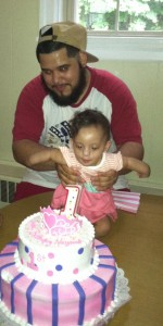 Nayana blowing out the candle with daddy's help
